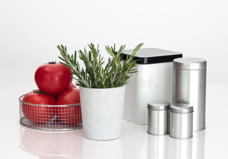 Food storage containers, tomatoes and rosemary. On white background royalty free stock image