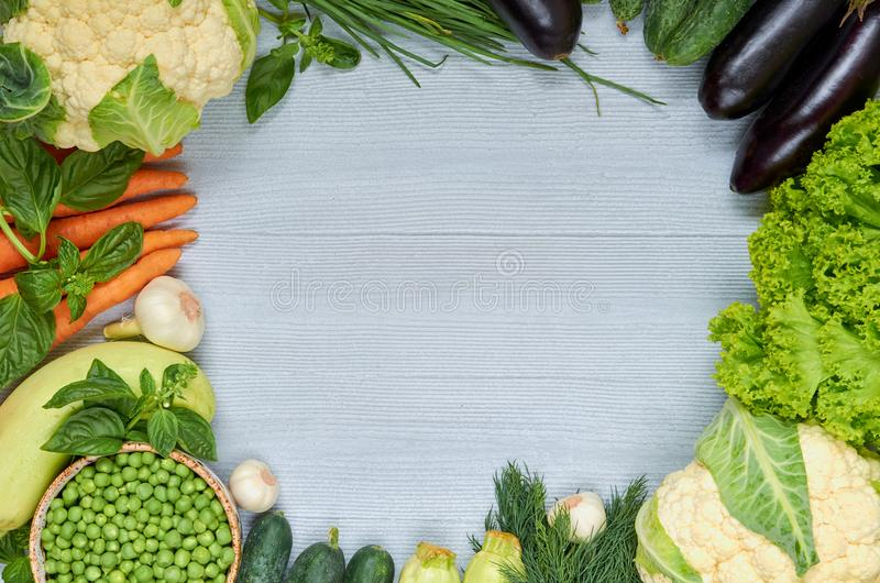 Food summer background with copy space for text. Fresh organic vegetables: carrots, zucchini, eggplants, basil - raw ingredients stock image