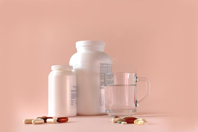 Food supplements, glass of water, and different supplement capsules on a pinky beige background. Two bottles of food supplements, glass of water, and different royalty free stock photography