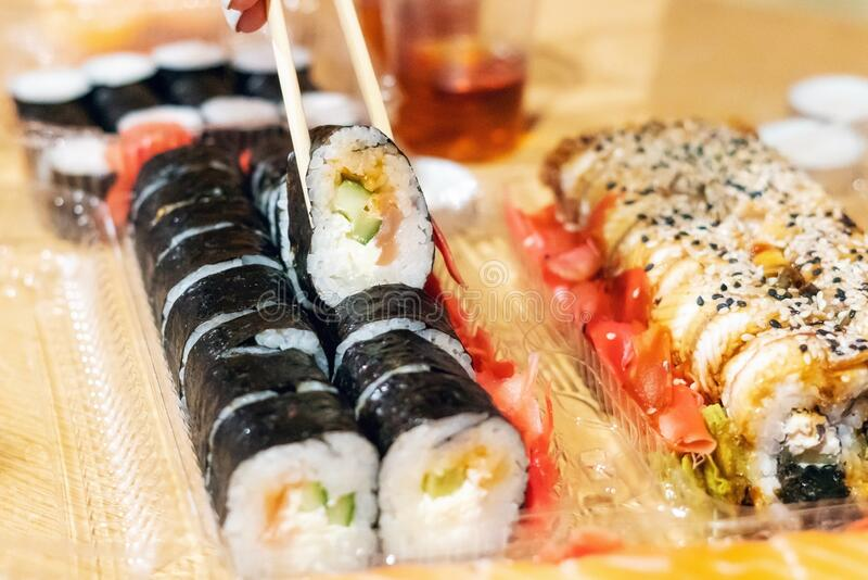 Food sushi roll, hand with chopsticks close-up.  stock photo