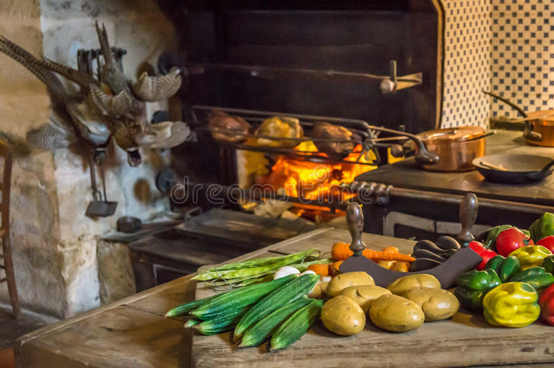 Food on the table for a meal as prepared in the Middle Ages. Fireplace in the background stock photography