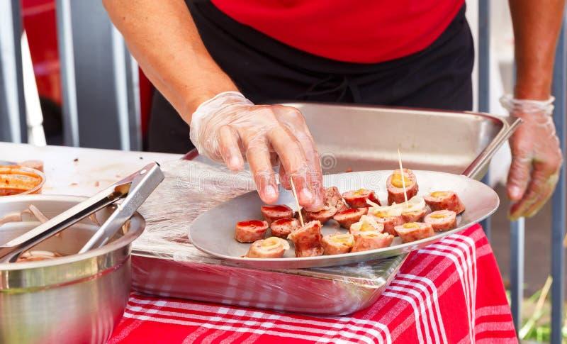 Food Tasting. Man preparing sausage at n outdoor food tasting event stock photos