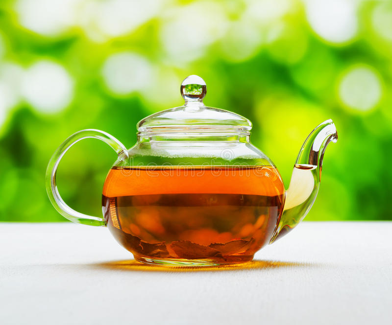 Teapot of fresh tea on natural background royalty free stock photography
