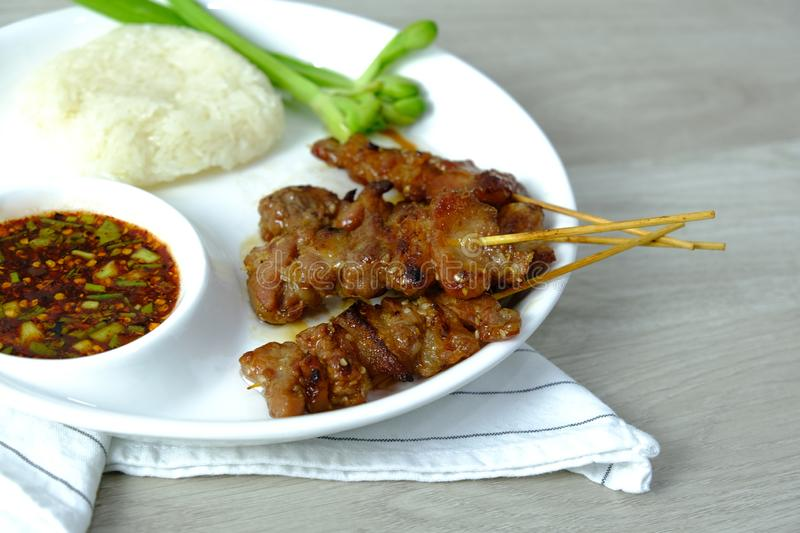 A food of Thailand. Barbecued Pork grill menu with sticky rice and spicy chilli soy sauce recipe and green vegetable on white stock photo