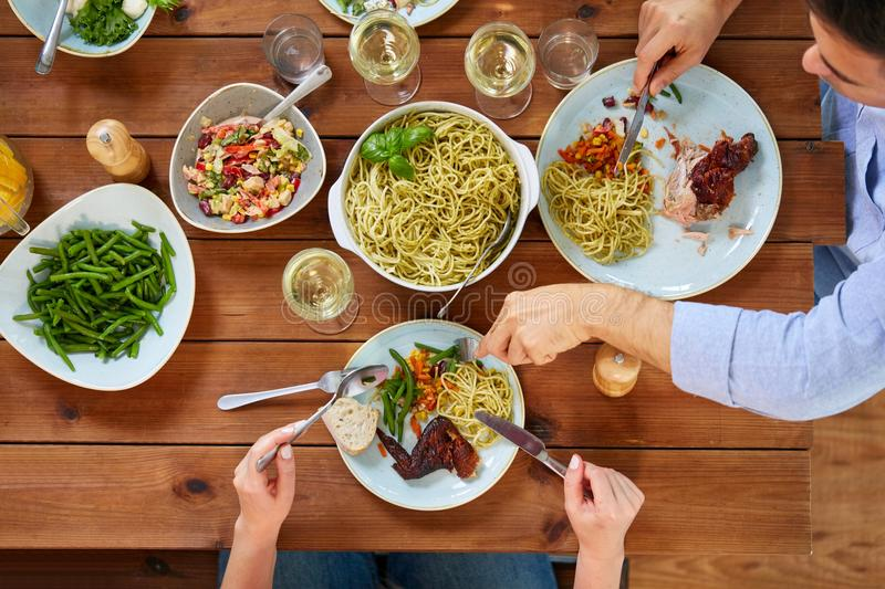 Couple at table with food eating pasta and chicken. Food, thanksgiving day and leisure concept - people eating pasta and chicken for dinner royalty free stock photos