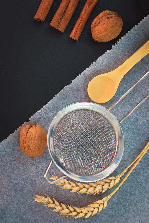 Food tools Preparing for bake the bakery - flour or sugar filter, wood tea spoon, baking paper, walnuts and wheat ears stock photos