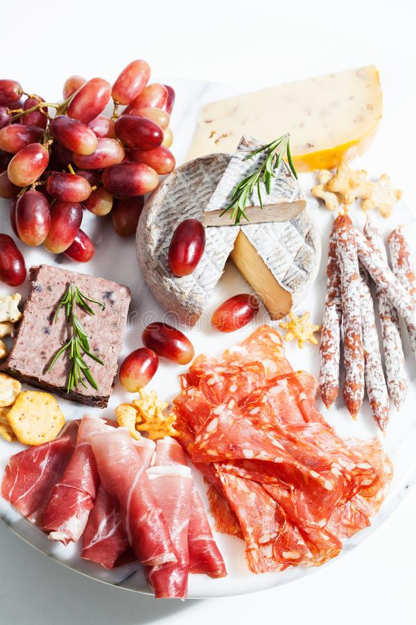 Food tray with charcuterie assortment, cheese and grapes. Appetizers royalty free stock images
