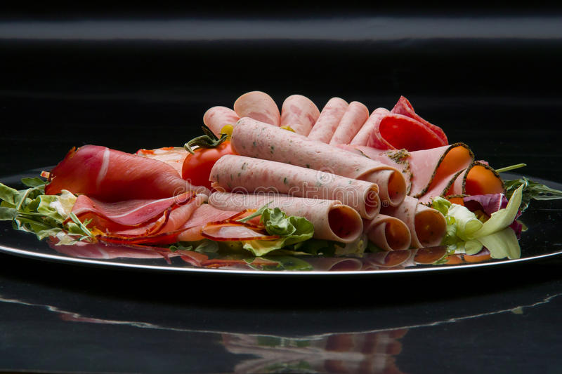 Food tray with delicious salami, pieces of sliced ham, sausage, tomatoes, salad and vegetable - royalty free stock image