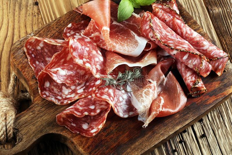 Food tray with delicious salami, raw ham and italian crudo or jamon. Meat platter with selection royalty free stock photography