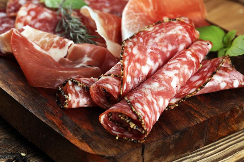 Food tray with delicious salami, raw ham and italian crudo or jamon. Meat platter with selection royalty free stock photos