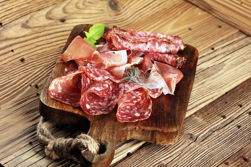 Food tray with delicious salami, raw ham and italian crudo or jamon. Meat platter with selection stock images