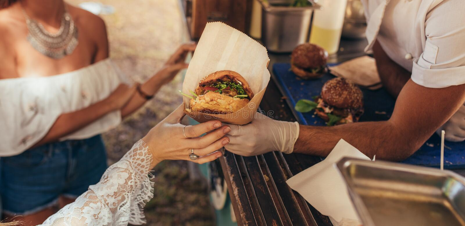 Food truck burger. Woman hand reaching for a burger at food truck. Closeup of food truck salesman serving burger to female customer stock image