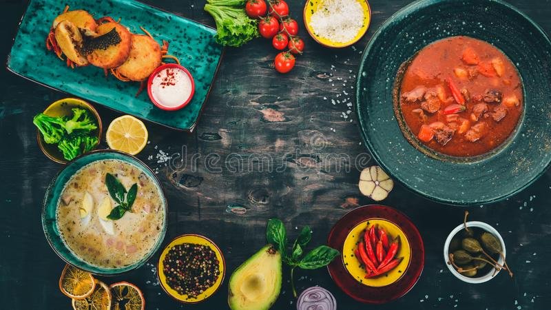 Food on a wooden table. Tomato soup, creamy soup, potato pancakes with cabbage. Top view. royalty free stock image