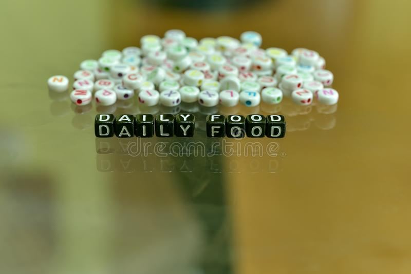 DAILY FOOD  written with Acrylic Black cube with white Alphabet Beads on the Glass Background.  royalty free stock photos