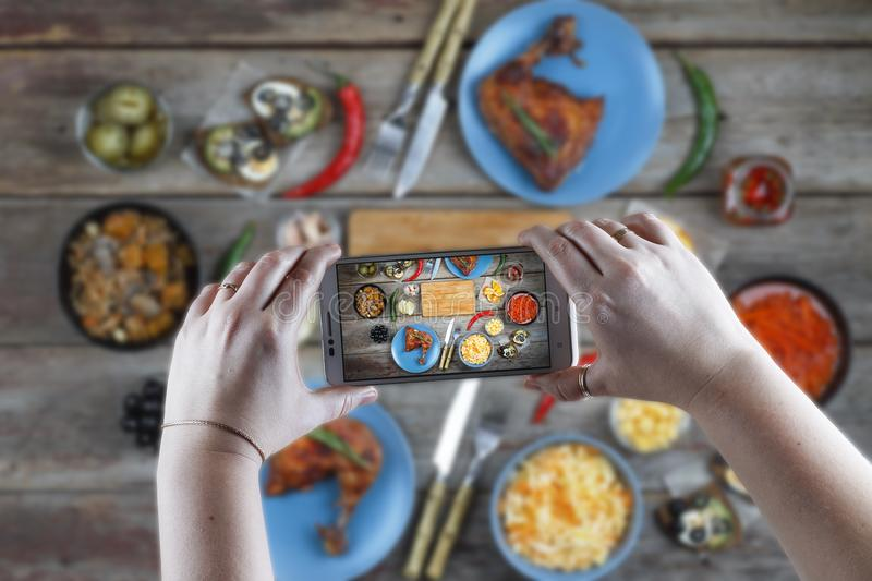 Food, taking pictures, eating out, eating in a cafe, technology, food, people, young woman, dining. Food. A young woman is taking pictures a dining table with a royalty free stock photo