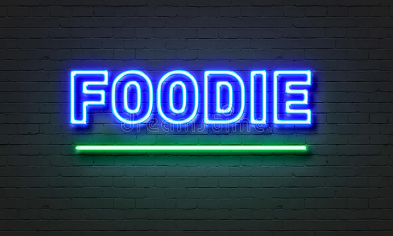 Foodie neon sign on brick wall background. Foodie neon sign on brick wall background royalty free stock image