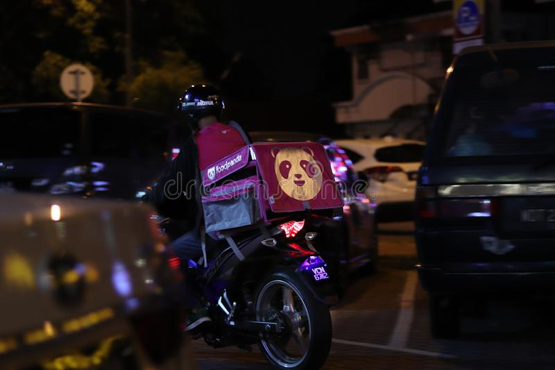 Foodpanda Delivery Man On His Motorbike In Ipoh. A Foodpanda courier delivery man in the streets of Ipoh, Malaysia at night royalty free stock photo