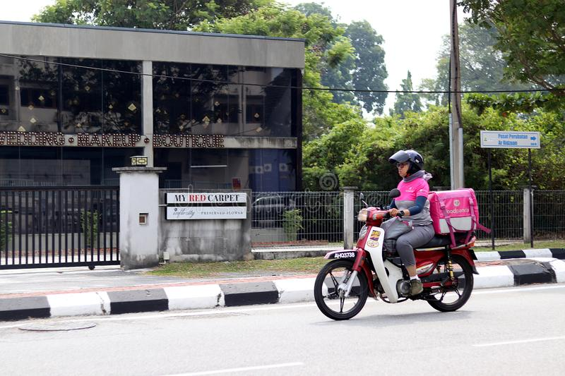 Foodpanda Malay Delivery Woman On Her Motorbike. A Foodpanda Malay courier delivery woman in the streets of Ipoh, Malaysia royalty free stock photos