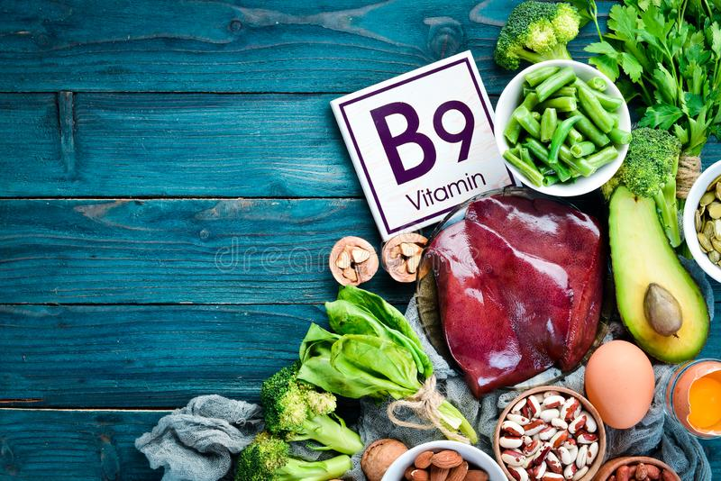 Foods that contain natural vitamin B9: Liver, avocado, broccoli, spinach, parsley, beans, nuts, on a blue background. Top view stock photos