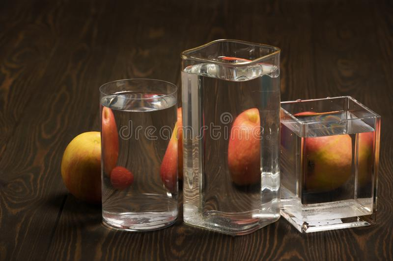 Foods distorted through liquid and glass on dark wooden background. Perspective, fractured and skewed images of common foods as seen through vessels filled with stock image