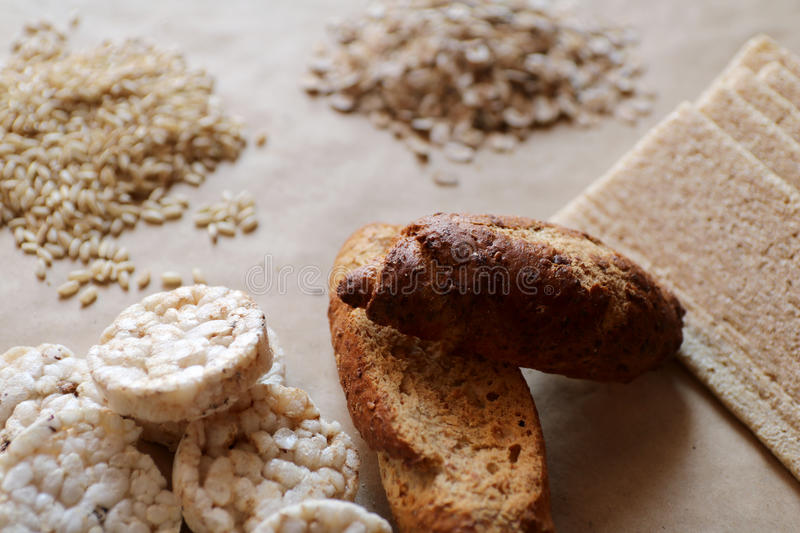 Foods high in carbohydrate. Healthy eating, diet concept. Bread, rice cakes, brown rice, oats. Oats and rice. Rice cakes and bread in background. Foods high in royalty free stock images