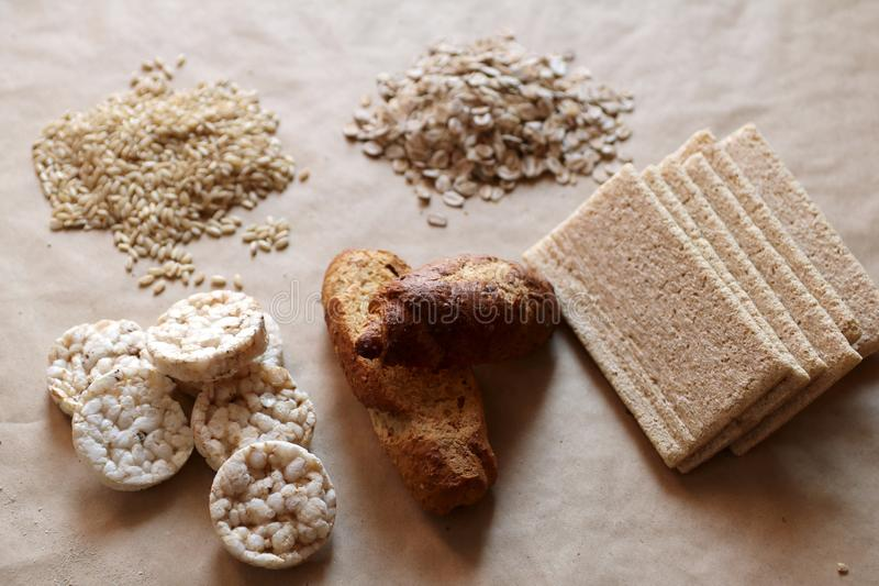 Foods high in carbohydrate. Healthy eating, diet concept. Bread, rice cakes, brown rice, oats. Oats and rice in a bowl. Rice cakes and bread in background stock images