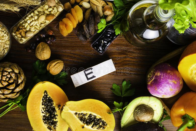 Foods som är rika i vitamin E liksom olja för vetebakterien eller olivolja, torkade aprikors, sörjer muttrar, papayaen, hasselnöt royaltyfri fotografi
