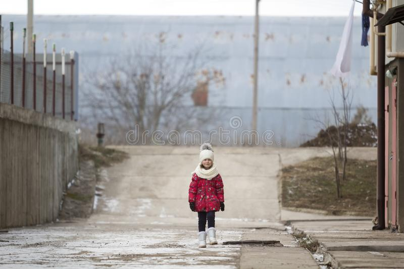 Fool-length portrait of cute little young funny pretty child girl in nice warm winter clothing walking confidently alone on white stock photography