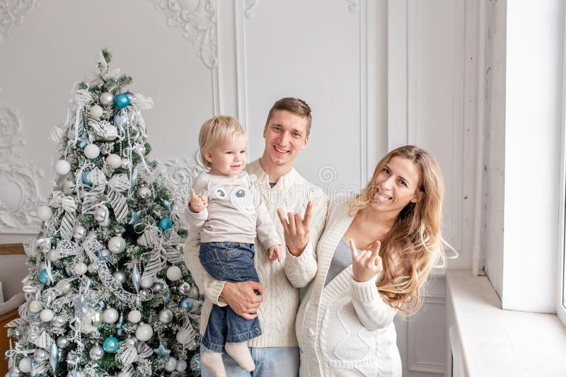 Fooling around on camera. Happy family Portrait In Home - father, pregnant mother and their little son. Happy new year. Happy family having fun at home stock photos