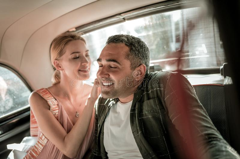 Smiling woman tickling neck of her husband. stock photo
