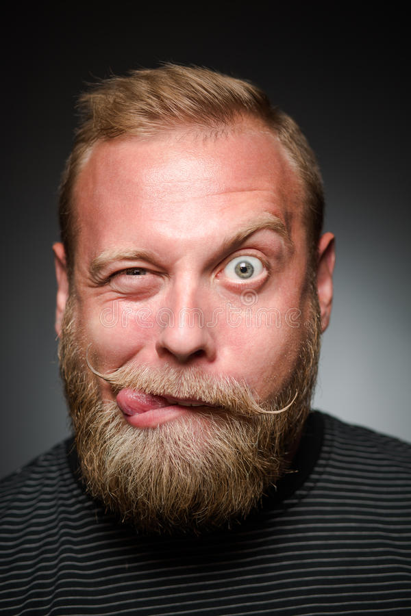 Fooling bearded man. In photostudio. Man with short blond hair making funny faces on black background royalty free stock photo