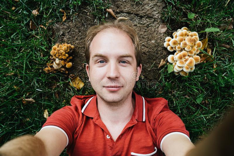 A foolish man in a red shirt lies on the ground between mushrooms royalty free stock photo
