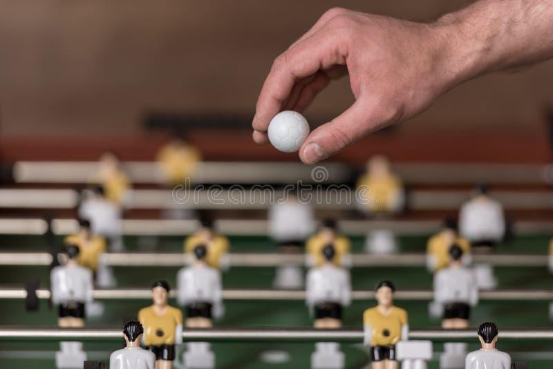 Foosball y mano con la bola, foco selectivo foto de archivo libre de regalías