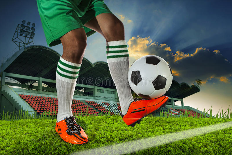 Foot ball player holding foot ball on leg ankle on soccer sport. Field agianst stadium and dusky sky use for soccer footbal teaml competition royalty free stock image
