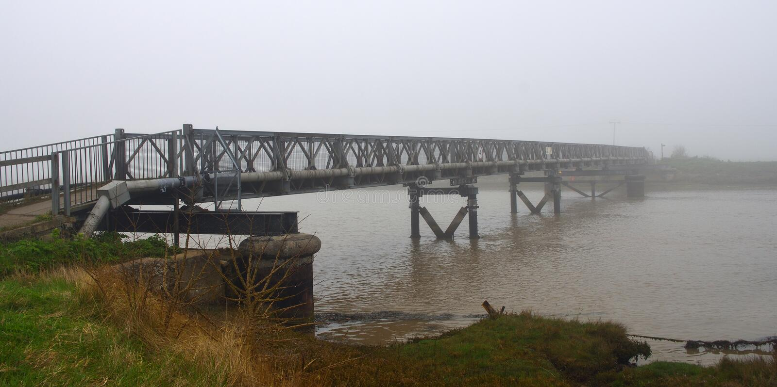 Foot Bridge over the River Blyth in the Fog. stock image