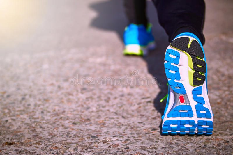 Foot closeup athlete running in sneakers outdoors. stock images