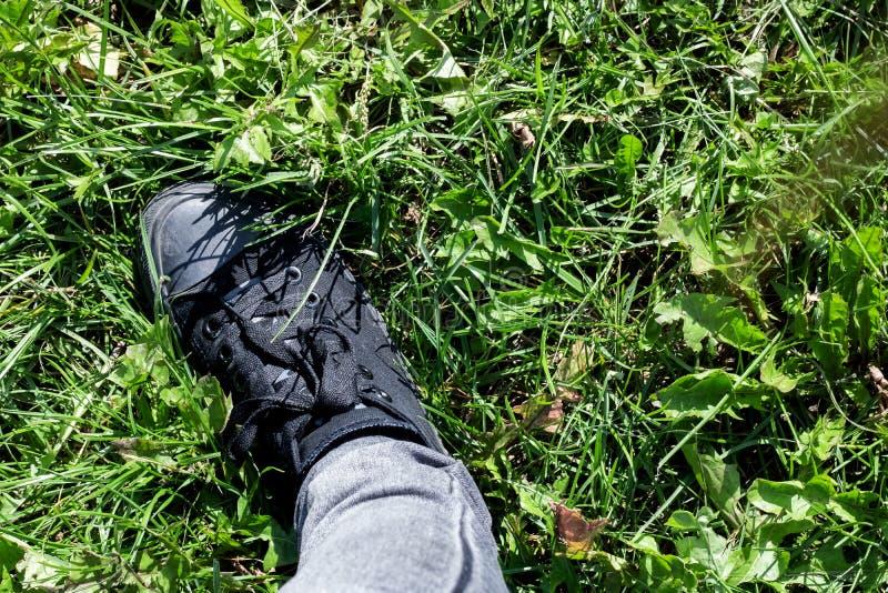 Foot in einem schwarzen Stiefel auf dem Gras stockfotografie