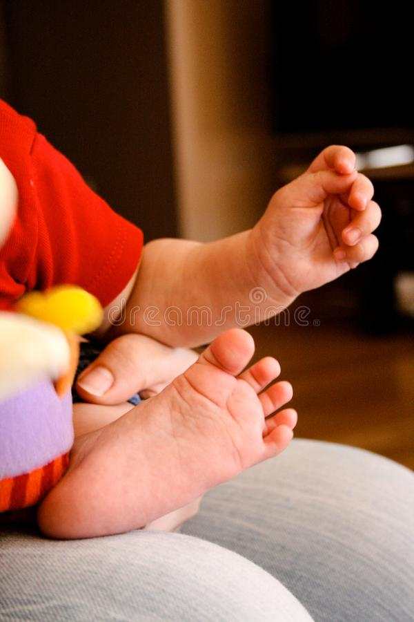 Foot and hand of a baby held by his mother stock images