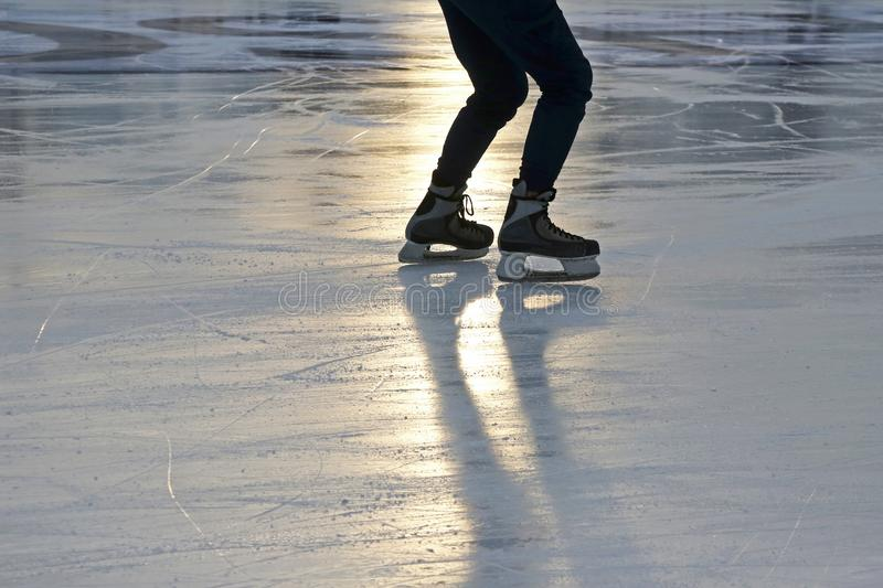 Foot ice-skating person on the rink in the sunlight. The foot ice-skating person on the rink in the sunlight stock images