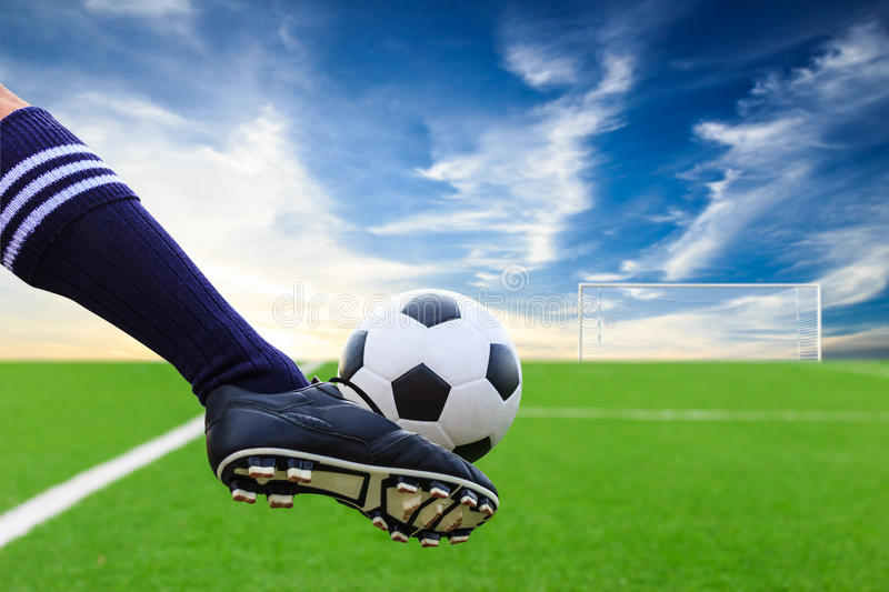 Foot kicking soccer ball. Against blue sky royalty free stock image