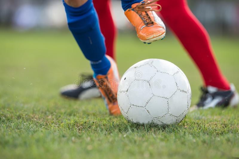 Foot kicking soccer ball on the field royalty free stock photos