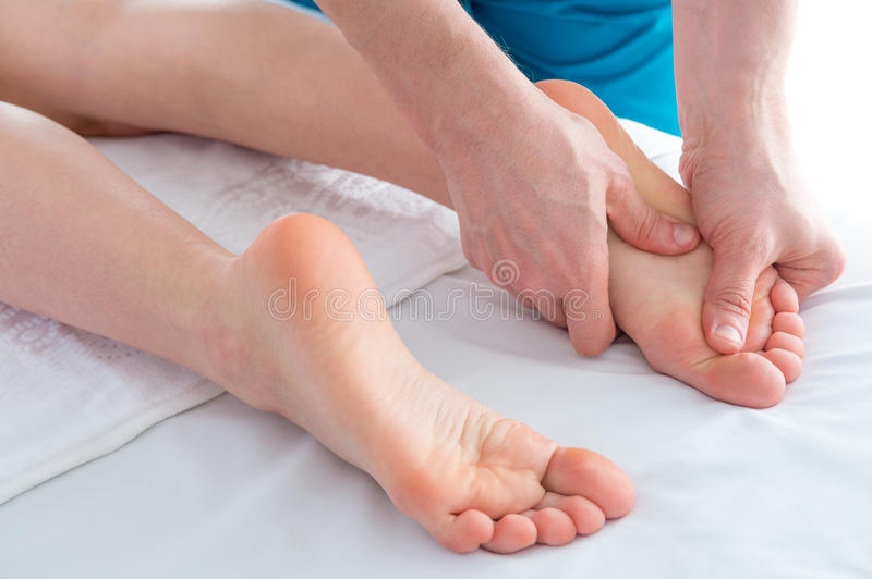 Foot and legs massage, alternative therapy, closeup studio shot stock image