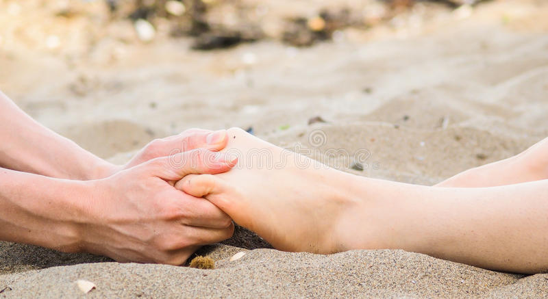 Foot massage in sand, male and female caucasian royalty free stock photos