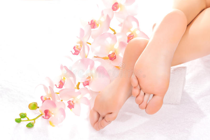 Foot massage in the spa salon. With orchid royalty free stock image