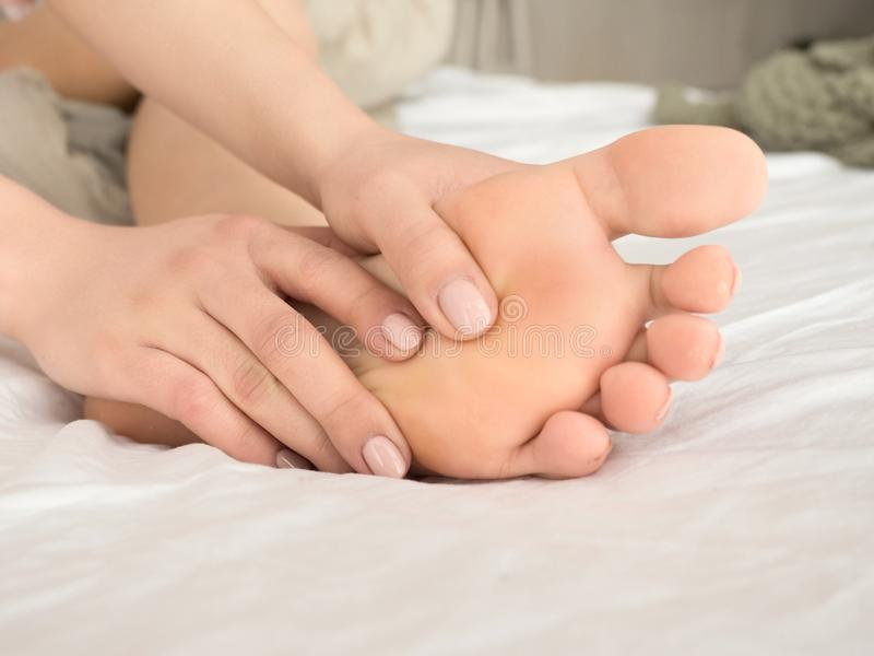 Foot Pain Leg of woman sitting on the bed in at home and fassaging her feet. Health care and spa concept stock photo