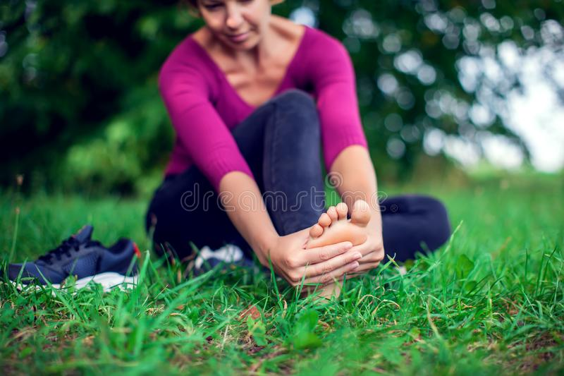 Foot pain .Woman sitting on grass .Her hand caught at the foot. stock image