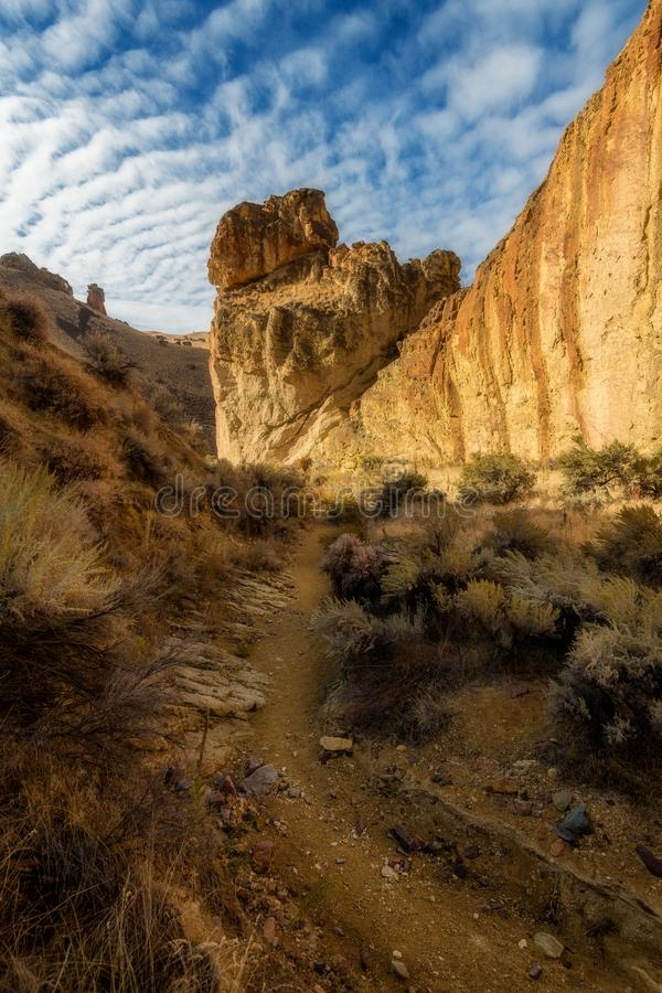 Foot path leads through a rocky canyon in a popular hiking place. Trail leads through a deep canyon in a desert rocky region stock photography