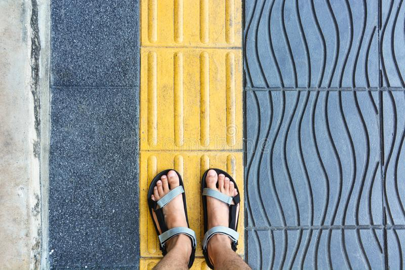 Foot on pedestrian lane for helping blind people royalty free stock images