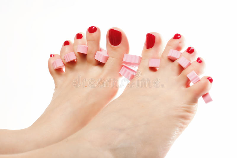 Foot pedicure applying red toenails on white royalty free stock images