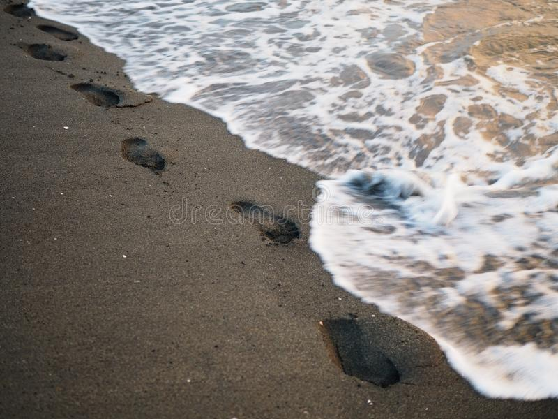 Foot prints on a black sand beach with tilt-shift blur. Surf in background. Concept for loneliness, solitude, depression stock photos